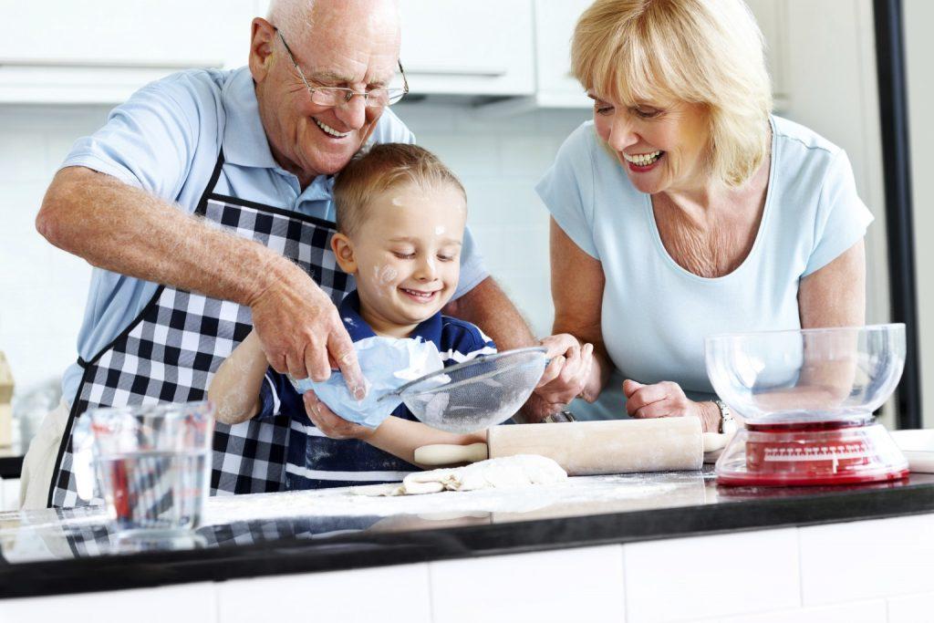 Senior couple and small kid preparing food